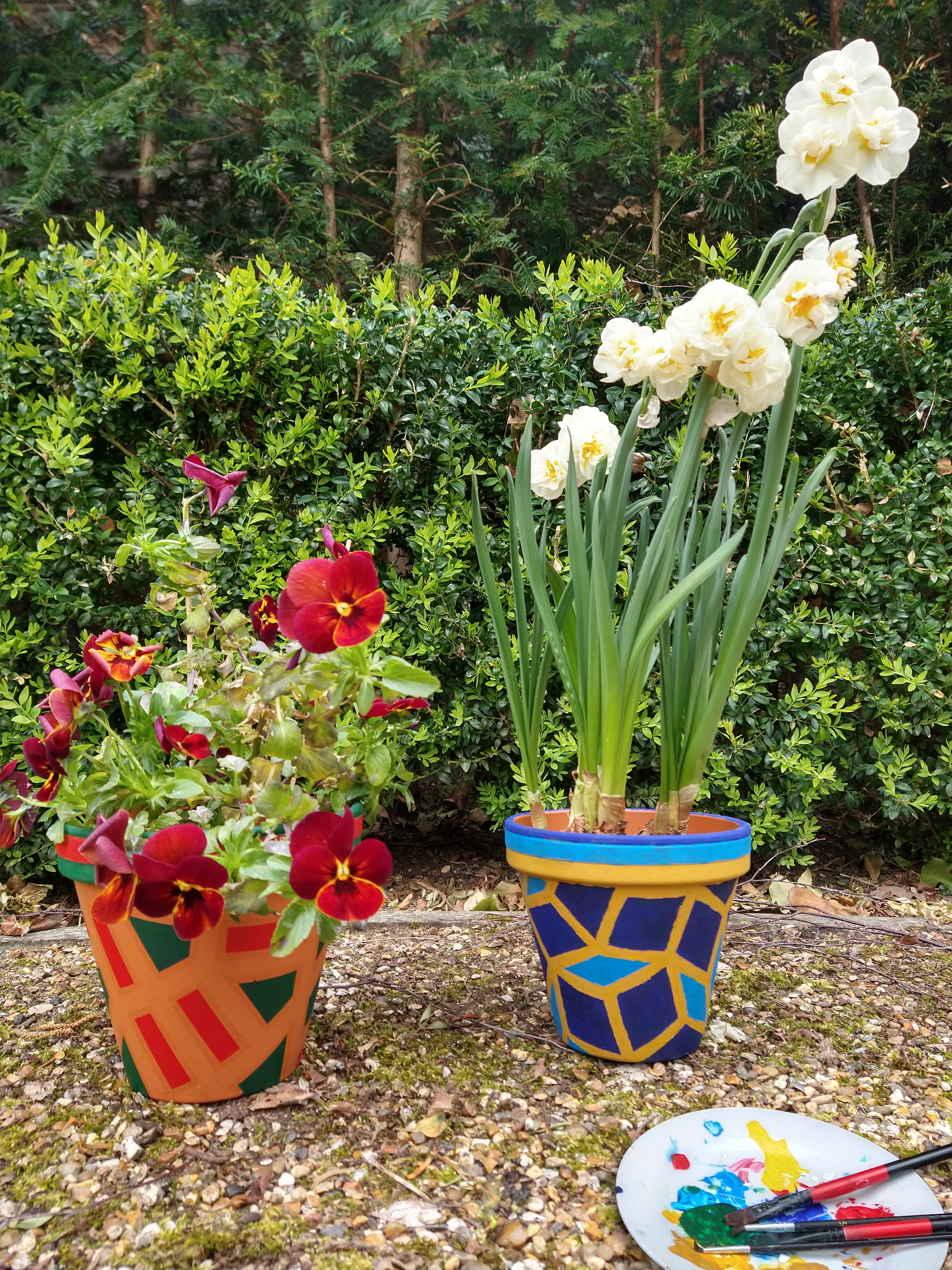 Flower pots painted in bright colours with aperiodic tiling patterns.