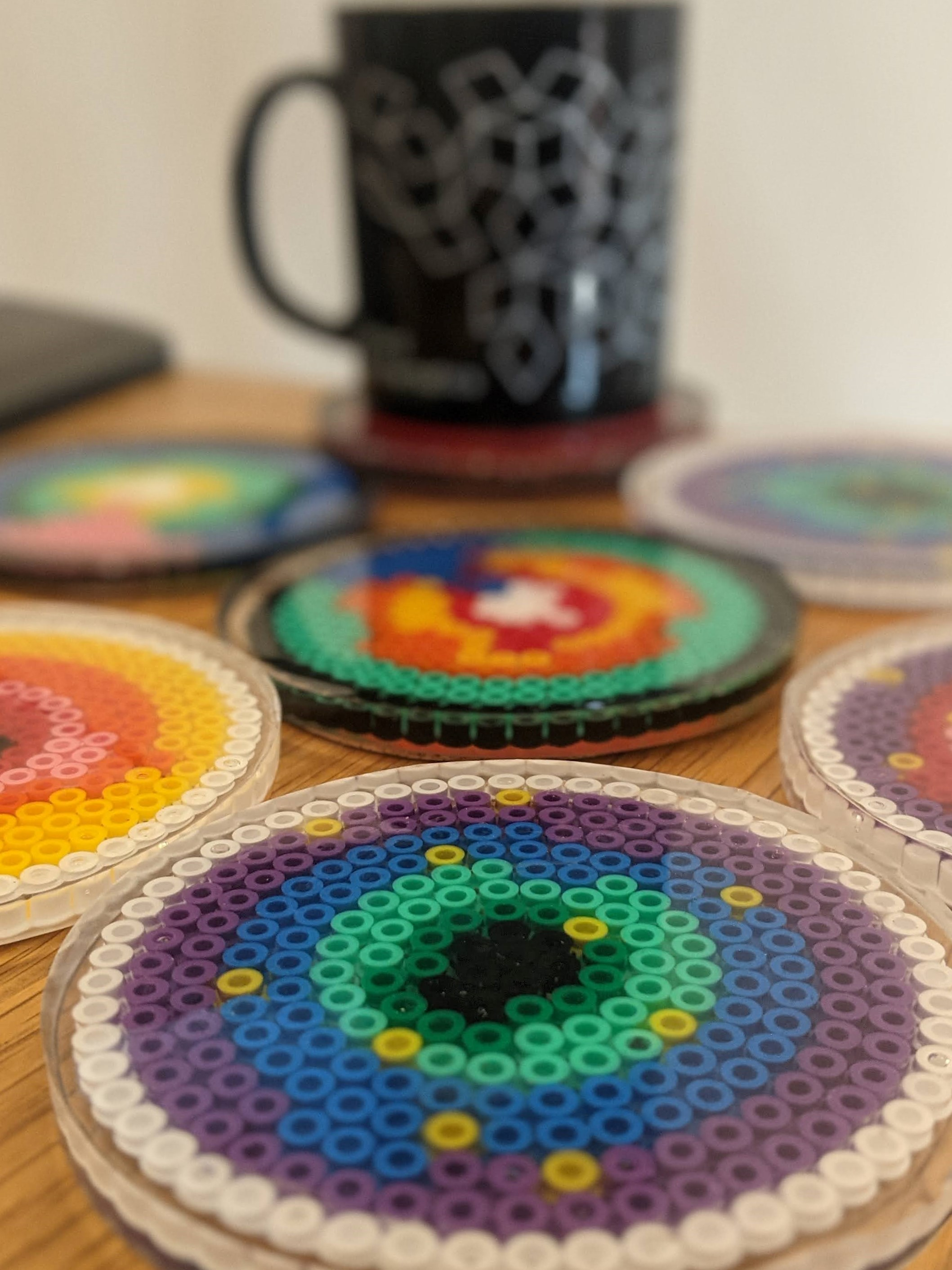 Coasters made from plastic beads in resin, showing show an agent-based model of microbeads infiltrating a tumour spheroid.